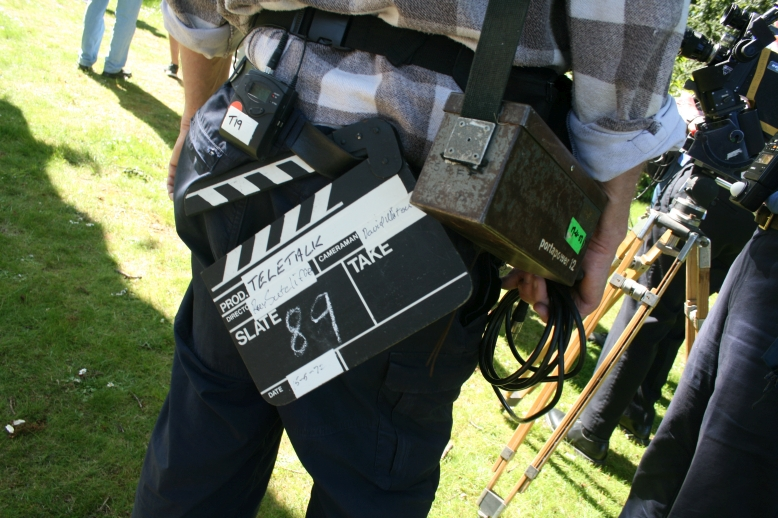 Assistant camera operator John Adderley with a clapperboard